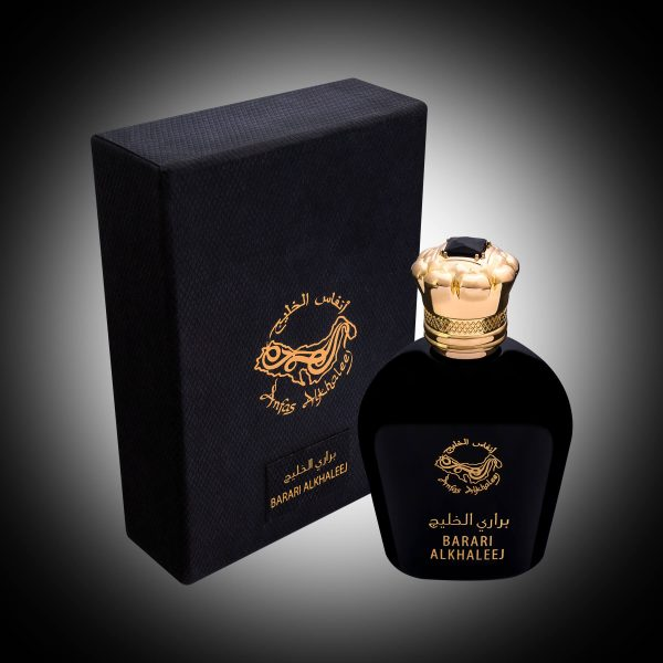 black perfume bottle with a gold cap next to a black leather box